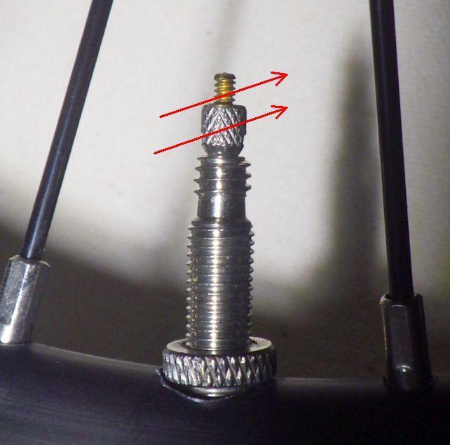 仏式バルブ。先端のネジを矢印方向に緩めないと空気が入らない。