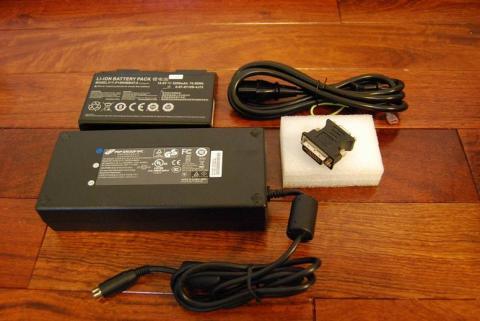 PC付属品。左上から時計回りでバッテリー、電源ケーブル、映像変換端子、電源アダプター。電源ケーブルと電源アダプターをくっつけると1200gになります。